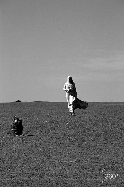 En marzo y abril del 2006, tuve la oportunidad de acompañar a un grupo de cineastas, fotógrafos y artistasescénicos al norte de África: Argelia y la República Árabe Saharaui Democrática, también conocida como el Sahara Occidental. La meta: Leyuad, en los territorios liberados del Sahara Occidental, no distante de Mauritania. Leyuad, es un lugar deshabitado rodeado de leyendas: tierra de fantasmas, hogar de la Yina, o sea la diablesa, paraje donde por las noches aparece el diablo. Es famoso localmente también por ser una zona cargada de magnetismo donde se cree confluyen los ecos de voces lejanas en tiempo y distancia. Nuestro guía en los más de mil quinientos kilómetros de arena fue Belga Moh Brahim beduino, filósofo, coleccionista, actor de teatro, padre de siete hijos y abuelo de numerosos nietos. Su presencia inmediatamente impuso respeto, por su serenidad, experiencia y sabiduría. Por sus silencios. Belga es de aquellas personas que sólo expresa lo realmente indispensable. Son muchísimas las enseñanzas que obtuvimos del desierto y otras más seguramente aparecerán con el tiempo. Cruzamos dunas y salinas. Un vasto y permanente horizonte de 360 grados salpicado de antiguas tumbas de gigantes, mares de fósiles y zoológicos atrapados en la piedra. También pasamos por los escombros de las casas de arena, paradójicamente derruidas por las últimas lluvias del desierto. En los campamentos de refugiados y en las jaimas perdidas en la inmensidad, bajo un mar de estrellas o de los hirientes rayos de sol, fuimos testigos de la sabiduría, la perseverancia y la tenacidad de este pueblo seguidor de nubes. Hombres y mujeres que en medio de la nada resisten como lo hacen las semillas de las plantas multicolores que brotan en el Sahara cuando finalmente llueve después de años y décadas de sequía. Durante nuestro viaje, en el camino, en cualquier jaima, ante el té, la leche de cabra, el perfume, los alimentos y el abrazo fraterno, nos confrontamos una